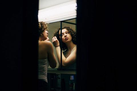 Sich schminkende Frau vor Spiegel