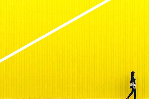 Frau vor gelber Containerwand
