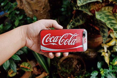 Hand mit Coca Cola Logo auf der Handyrückseite