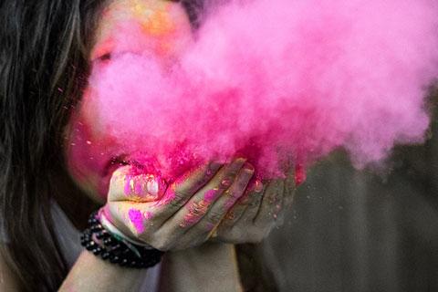 Frau pustet eine Wolke aus pinken Farbpigmenten